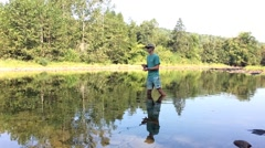 Young Man Standing in Pond and Casting Rod Stock Footage
