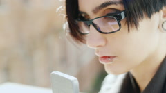 Close-up of attractive brunette in hipster glasses. Is typing on a mobile phone Stock Footage