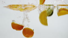 Oranges and Limes Falling into Water Stock Footage