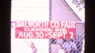 1963: people passing behind a fence with a walworth co. fair banner WALWORTH Stock Footage