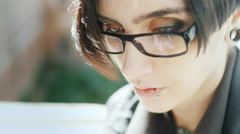 Portrait of an attractive brunette with a pierced lip. She is wearing glasses Stock Footage