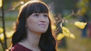 Portrait of young pregnant woman in red dress looking at camera in the autumn Stock Footage
