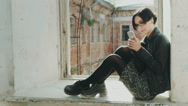 Young hipster woman sitting on a window sill in an old building. Using cell Stock Footage