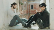 Young hipster couple sitting at the window, use mobile phones. Concept - the Stock Footage