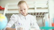 Girl sitting at a desk and writing something. Schoolgirl Stock Footage