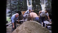 1960: men mixing cement in an old fashioned cement mixer WAUCONDA, ILLINOIS Stock Footage