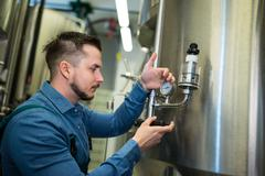 Attentive brewer checking pressure at brewery Stock Photos