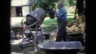 1960: men working with wheelbarrows and cement as well as cement mixer WAUCONDA Stock Footage