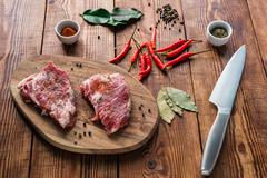 Meat with some condiment on kitchen table Stock Photos
