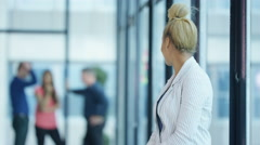 4K Portrait smiling casual businesswoman with coworkers standing in background Stock Footage