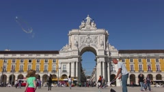 Playing with soap bubbles near Famous arch at the Praca do Comercio Stock Footage