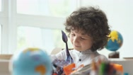Boy with black curly hair look book with pictures Stock Footage