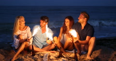 Cheerful Group of Friends Singing Lighting Sparklers Christmas Celebration Beach Stock Footage