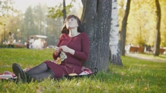 4K Cute happy pregnant woman in red dress sitting on blanket and stroking tummy Stock Footage