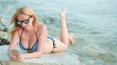 Girl on the beach using a smartphone. sexy woman in a bikini Stock Footage