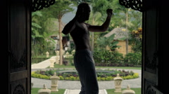 Young man dancing and listening to music on smartphone in villa entrance Stock Footage