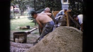 1960: a shirtless man on a construction site shoveling gravel WAUCONDA, ILLINOIS Stock Footage