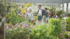 4K Friendly worker in garden center, watering the plants & talking to customer Stock Footage