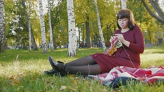 4K Cute happy pregnant woman in red dress sitting on blanket and make knitting Stock Footage