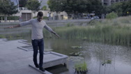 Man Balances, Arms Spread, Walks Along Edge Of Dock In City Park Stock Footage