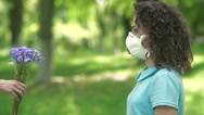 Girl in respirator give flowers. Stock Footage