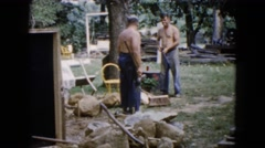 1960: two men working outside with rocks and sledgehammers WAUCONDA, ILLINOIS Stock Footage