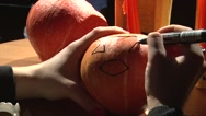 Drawing eyes and mouth on Halloween pumpkin to carve Stock Footage