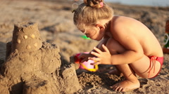Little girl builds a sand castle Stock Footage