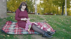 4K Cute happy pregnant woman in red dress sitting on blanket in the autumn park Stock Footage