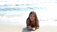Little girl lying on the sand, the sea waves splashing in her body Stock Footage
