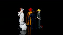 Rotating professional miniature people figures on black background Stock Footage