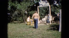 1960: spending time in the backyard with family and friend on swinging bench. Stock Footage