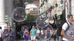 A man plays with soap bubbles near Famous arch at the Praca do Comercio Stock Footage