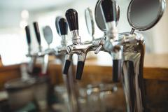 Row of chrome beer taps at cafe Stock Photos