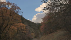 Time lapse-Clouds roll over mountain road - autumn colors Stock Footage