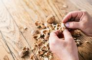 Hands of unrecognizable woman cracking walnuts, wooden table Stock Photos
