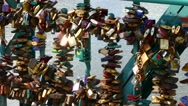 A pan over large number of padlocks on lovers bridge with river in background Stock Footage