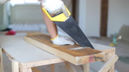 Close up shot of arms sawing through a wooden siding panel Stock Footage