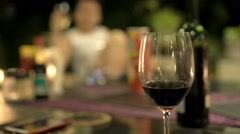 Glass of red wine, people in background during dinner at night Stock Footage