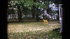 1960: person in long sleeves collects leaves in wheelbarrow and marches through Stock Footage