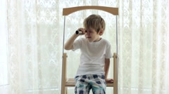Boy Sitting at Home on a Ladder and Looking Through a Telescope Stock Footage