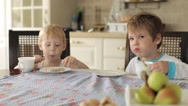 Brothers Sitting at the Kitchen Table With Tea and Sweets Stock Footage