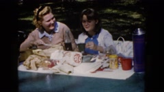 1960: two women outside at a table enjoying a picnic WAUCONDA, ILLINOIS Stock Footage