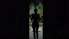 Young woman opening door and walking out on porch in country house Stock Footage
