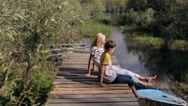 Mother and Son Sitting on a Wooden Pier Stock Footage
