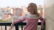 Woman Standing on the Balcony Overlooking the City Stock Footage