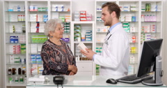 Young Pharmacist Man Talking Medicine Give Old Woman Patient Healthcare Counsel Stock Footage