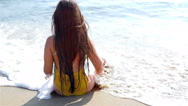 Little girl sitting on the sand by the sea, the waves splashing in her body Stock Footage