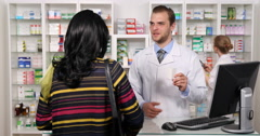 Young Woman in Pharmaceutics Shop Pharmacist Man Offer Medical Treatment Advice Stock Footage