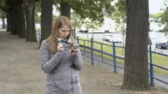 Girl catches Pokemon on cell phone game 4k Stock Footage